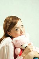 Woman in pajamas hugging teddy bear