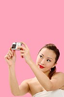 Woman taking self picture with digital camera