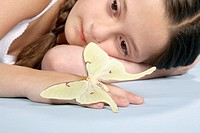 Girl 6-7 lying down with butterfly on hand, close-up