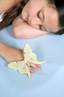 Girl 6-7 lying down with butterfly on hand