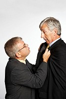 Short businessman grabbing tall colleague by jacket, side view