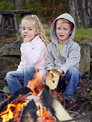 Young boy and young girl cooking toast over a fire at a campsite