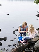 Woman and young girl collecting pebbles by a lake
