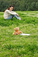 Woman sitting on the grass looking at her teddy bear