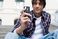 Teenage boy using a camera telephone