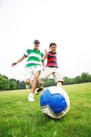 Father and son playing soccer in the park