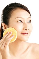 Woman cleaning her face using facial sponge