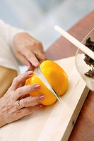 Hand of senior woman cutting yellow capsicum