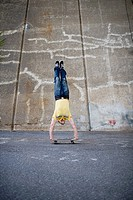 A man doing handstands on a skateboard