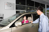 Woman and salesman in car showroom