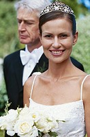 Bride smiling with mature man standing in behind