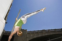 Acrobat hanging from pole
