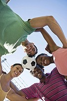 Group of adults huddled with soccer ball