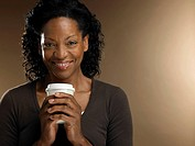 Mature woman holding disposable cup, smiling, portrait