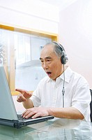 Senior man with headphones using laptop
