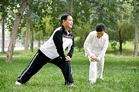 Senior man and woman exercising in the park