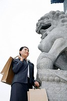 Businesswoman standing next to a lion statue, carrying paper bags