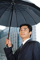 Businessman holding a black umbrella