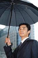 Businessman holding a black umbrella