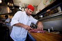 Chef trimming meat fillet in restaurant kitchen