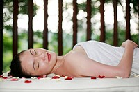 Woman in towel lying down around flower petals