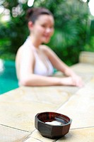 Wooden bowl with woman in bikini by the poolside in the background