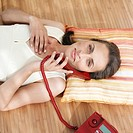Woman using telephone, lying on wooden floor, portrait