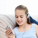 Girl 10-11 sitting on sofa, using mp3 player focus on foreground