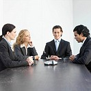 Four business people sitting at desk using Conference Phone