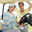 Portrait of couple in golf buggy