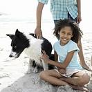 Boy and girl 10-13 with dog on beach