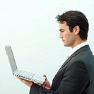 Young businessman holding and looking at laptop, profile, upper half
