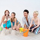 Family including boy and girl 11-13 building sandcastles and laughing