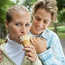 Young couple eating ice cream in park