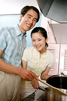 Mature man and woman smiling at the camera while cooking in the kitchen