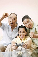 Senior man and woman cheering as her woman playing video game console