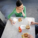 Woman eating fast food outdoors, high angle view
