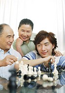 Men playing chess game with senior woman watching