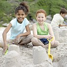 Two girls 12-13 building sandcastles on beach, smiling, portrait