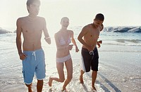 Young woman and two young men in swimwear running on beach