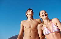 Young semi-dressed couple against sky, upper half, low angle view