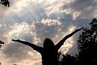 Girl with arms upstretched toward sunset, Assiniboine Park, Winnipeg, Canada
