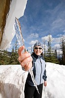 A woman grabs an icicle from the roof of a winter cabin, Silver Star ski resort near Vernon, BC, Canada