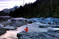 Girl seated on rock looking at river, sunset, Vancouver Island, Canada