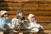 Three preteen or teen girls standing on deck of log cabin, looking away, low angle view