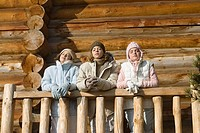 Three preteen or teen girls standing on deck of log cabin, eyes closed, low angle view