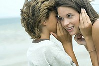 Boy whispering in teen sister's ear, close-up
