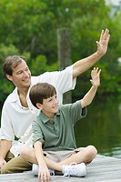 Father and son sitting on dock and waving together