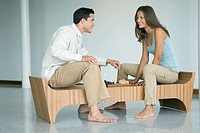 Young couple playing chess, smiling at each other