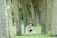 Woman sitting in palm grove reading book